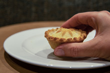 Hand Of Woman Taking Christmas Mince Pie. Fruit Mince Pies For Festive, Winter Season.  Mince Pie On White Plate. Holidays Concept. Selective Focus. Delicious.