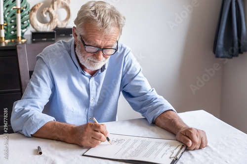 Fotomural  Senior old man elderly examining and signing last will and testament; document is mock-up