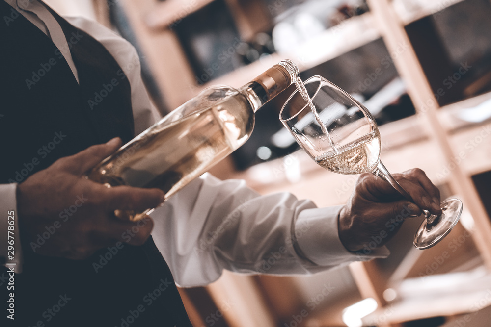 Fototapety, obrazy: Sommelier Concept. Senior man standing pouring white wine into glass elegant close-up