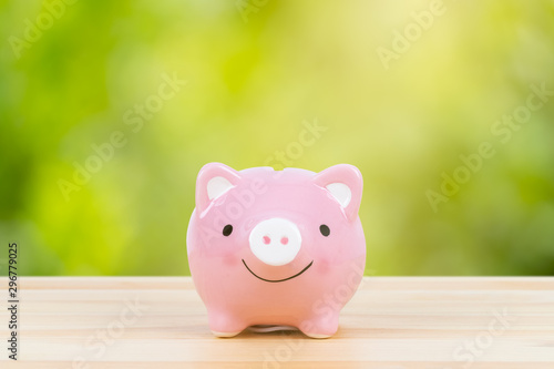Fotomural  Pink piggy bank on wooden desk with sunlight ray, on green tree background, savi