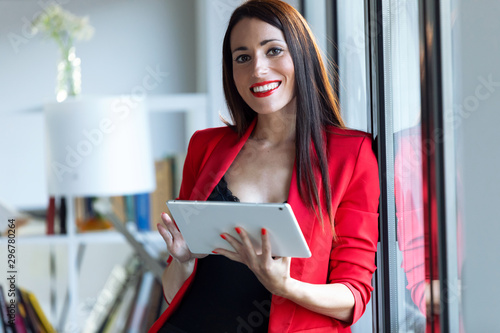 Billede på lærred Pretty young businesswoman looking at camera while using her digital tablet in the office