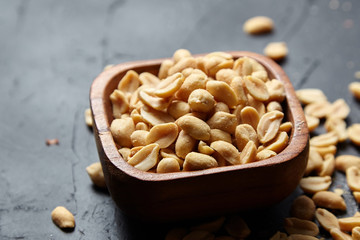 Wooden bowl with roasted peeled peanuts, salty beer snack on dark background