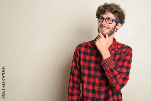 Photo  Happy young bearded hipster man with curly hair thinking