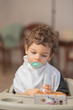 Concept of innocence and child tranquillity. Portrait of a beautiful child with brown hair and a pacifier in the mouth, with the background out of focus.
