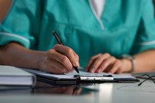 Cropped View Of Nurse In Uniform Writing In Clipboard During Night Shift