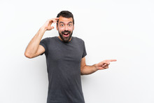 Young Handsome Man Over Isolated White Background Surprised And Pointing Finger To The Side