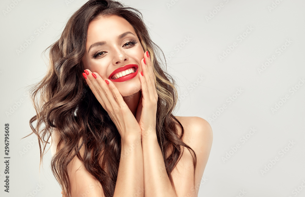 Fototapeta Beautiful laughing brunette model  girl  with long curly  hair . Smiling  woman hairstyle wavy curls . Red  lips and  nails manicure .    Fashion , beauty and make up portrait - obraz na płótnie