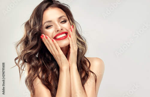 Obraz Beautiful laughing brunette model  girl  with long curly  hair . Smiling  woman hairstyle wavy curls . Red  lips and  nails manicure .    Fashion , beauty and make up portrait - fototapety do salonu