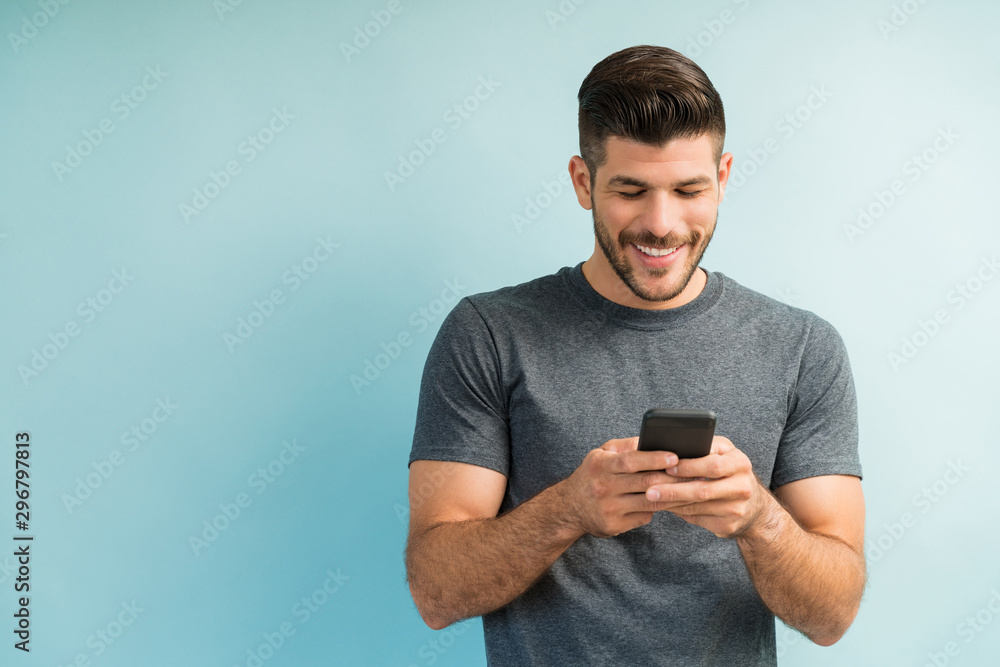 Fototapeta Attractive Hispanic Male Surfing On Mobile Phone