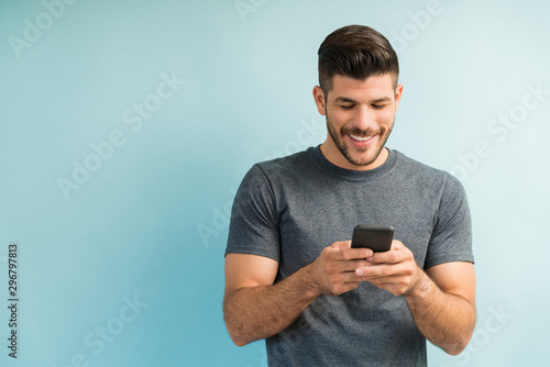 Photo  Attractive Hispanic Male Surfing On Mobile Phone