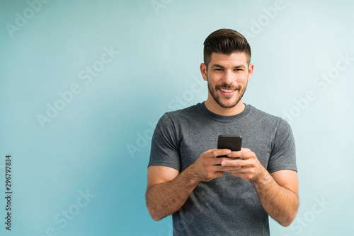 Valokuvatapetti Handsome Man Texting On Smartphone Against Turquoise Background