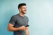 Leinwanddruck Bild - Good Looking Latin Man Standing With Smartphone