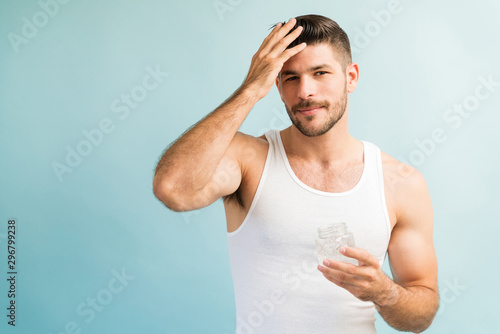 Fotomural  Handsome Latin Muscular Man Setting Hairstyle In Studio