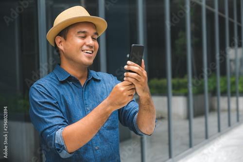 Foto  Young asian man using smartphone.