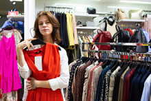 Thoughtful Woman Holding Red Dress In Clothing Shop