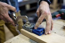 Woodwork And Furniture Making Concept. Caucasain Man Carpenter Installs The Furniture Hinge. Pocket Hole Joinery Concept.