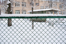 Snow-covered Rabitz Grid. Lattice Fence Covered With Fresh Snow. Background Is Building.
