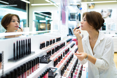 Pinturas sobre lienzo  Young woman puts on red lipstick at cosmetics shop