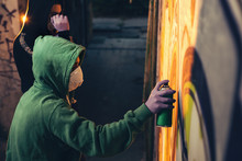 Street Artist Painting Colorful Graffiti On A Wall.