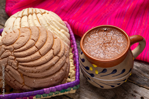 Mexican hot chocolate with sweet conchas bread on wooden background