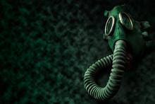 Armageddon, Biological Warfare And Post Apocalyptic Survivor Conceptual Idea With Green Rubber Gas Mask Surrounded By Toxic Smoke And Radioactive Dust On Dark Grungy Background With Copy Space