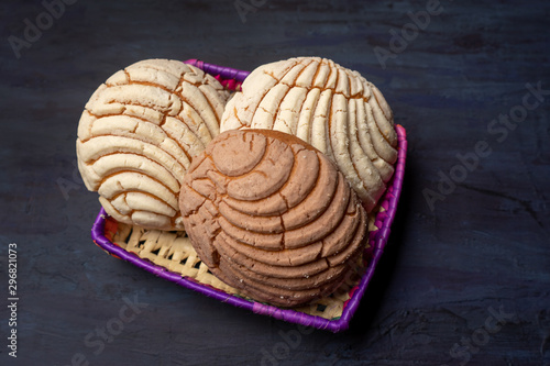 Photographie Mexican sweet bread: vanilla and chocolate conchas on dark background