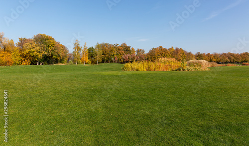 Foto auf Gartenposter Himmelblau Autumn in the park and breathtaking view on the golf course.