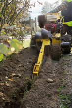 Motor Chain Trencher In Action, Dig Machine Construction Site Equipment For Laying Cables In Narrow Trenches In The Ground, Selected Focus, Motion Blur