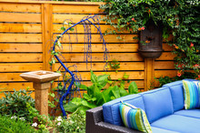 Detail Of A Relaxing Modern Urban Garden, With Horizontal Asian Inspired Cedar Fencing, Low Maintenance Planting, A Fountain And Bird Bath. Comfortable Patio Furniture Adds Style.