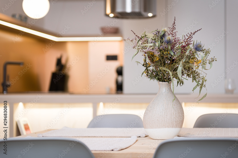 Fototapeta Vase on dining table of contemporary apartment, kitchen in background