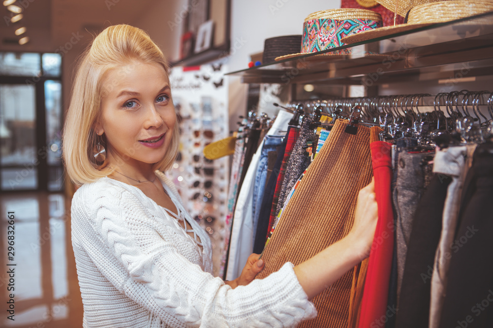 Fototapeta Happy beautiful woman smiling to the camera while choosing clothes to try at local fashion store
