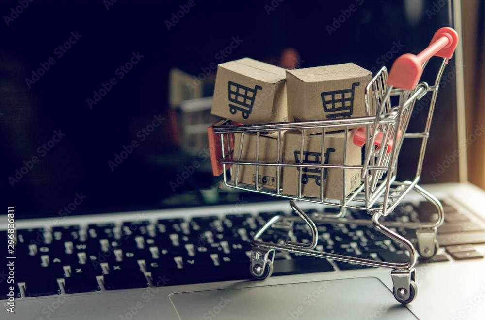 Fototapeta Shopping online. cardboard box with a shopping cart logo in a trolley on a laptop keyboard. Shopping service on The online web. offers home delivery..