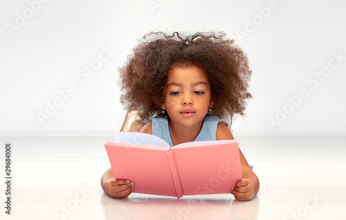 Obraz na plátně childhood, school and education concept - little african american girl reading b
