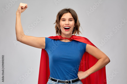 women's power and people concept - happy woman in red superhero cape showing arm bicep muscle over grey background