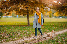 Woman And Dog Walking In The Park In Autumn