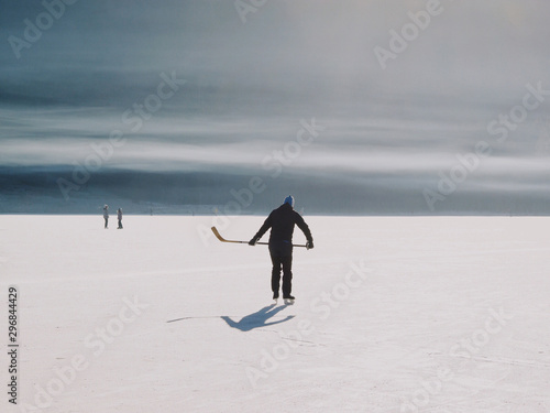 Group of people playing ice hockey on frozen lake