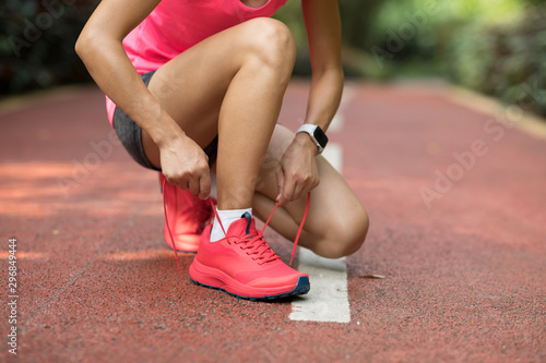 Photographie Female runner tying shoelace before running on park trail