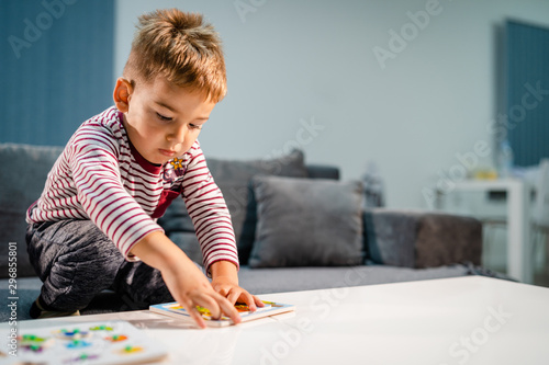 Fotografia Small boy little playing at home alone by the table with puzzle developing menta