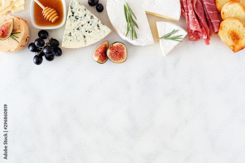 Fototapety, obrazy: Assorted cheeses and meat appetizers. Top border, overhead view on a white marble background with copy space.