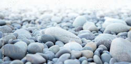 Round stones on a dry river bed outside in nature. Smooth pebbles with light gray tones in ambient light.