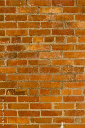 Deteriorating old red clay brick wall texture with stray shadows