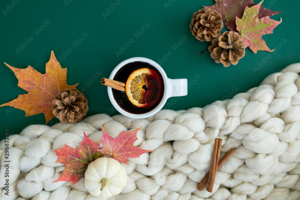 Fototapety, obrazy: Spiced cider with orange and cinnamon on green background with fall leaves and pinecones, chunky wool knit blanket