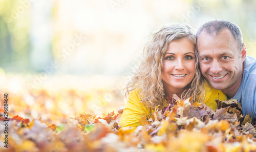 Happy senior couple lying in autumn maple leaves Fototapet