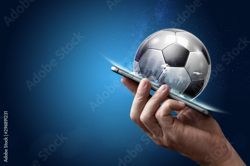 Foto Smartphone in hand with a 3D soccer ball on a blue background