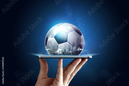 Fotografia Smartphone in hand with a 3D soccer ball on a blue background