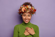 canvas print picture - Candid shot of attractive smiling woman feels thankful, promises be loyal, appreciates pleasant gift, touches chest gratefully, wears autumn wreath, values somebodys offer, poses indoor in casual wear