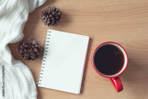 notebook with coffee,pine cone and white sweater on wood table background,office desk. Autumn and winter concept. - 296898819