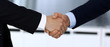 Business people shaking hands after contract signing in modern office. Unknown businessman, male entrepreneur with colleagues at meeting or negotiation. Teamwork, partnership and handshake concept