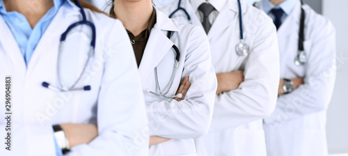 Group of modern doctors standing as a team with arms crossed in hospital office Wallpaper Mural