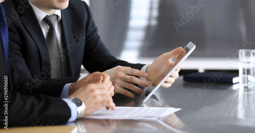Fototapeta Businessman using tablet computer and work together with his colleague or partner at the glass desk in modern office, close-up. Unknown business people at meeting. Teamwork and partnership concept obraz na płótnie